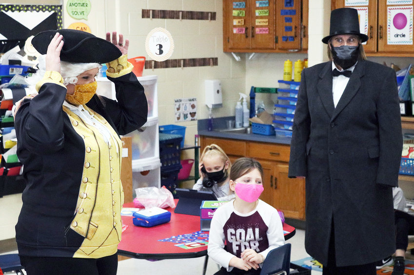 Skyline Elementary School kindergartner Shelby Graham, center, discusses the differences between George Washington's tricorn hat and Abraham Lincoln's stovepipe hat during the Tuesday, Feb. 23, lesson about the presidents. Teacher Jessica Lutjen, left, portrayed Washington while teacher Tina Emery, right, was Lincoln.