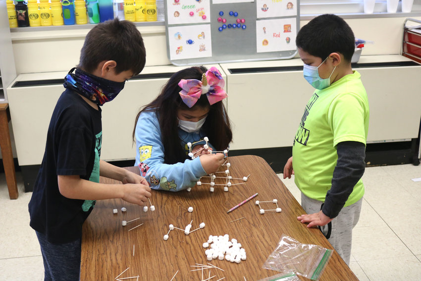 From left, Milo Mitts, Marisol Ramirez, and Erick Tobarubaldo, students in Mary Houston's second grade class, compete to build the tallest structure using 100 marshmallows and 100 toothpicks in honor of the 100th day of school on Tuesday at Washington Elementary. A number of Sedalia School District 200 schools celebrated the milestone with fun activities.