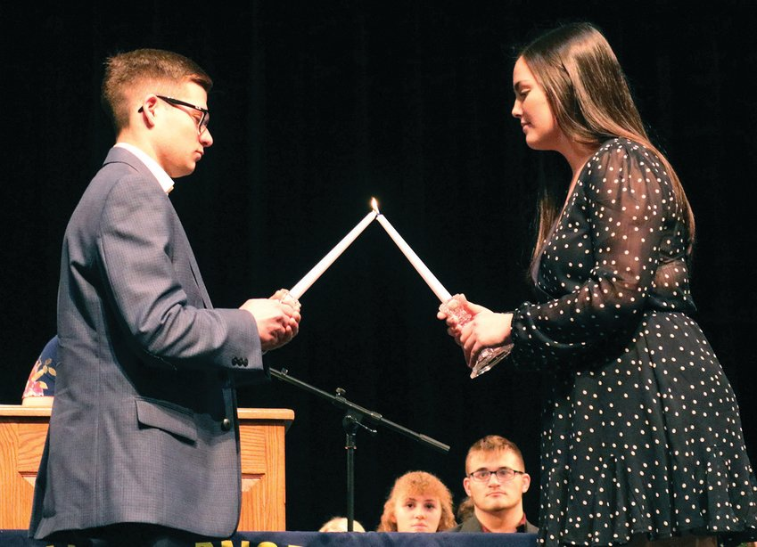 Outgoing Smith-Cotton National Honor Society President Breanna Hoover, right, passes the mantle of leadership to incoming President Ethan Daly during a ceremony March 10, 2020, in the Heckart Performing Arts Center.