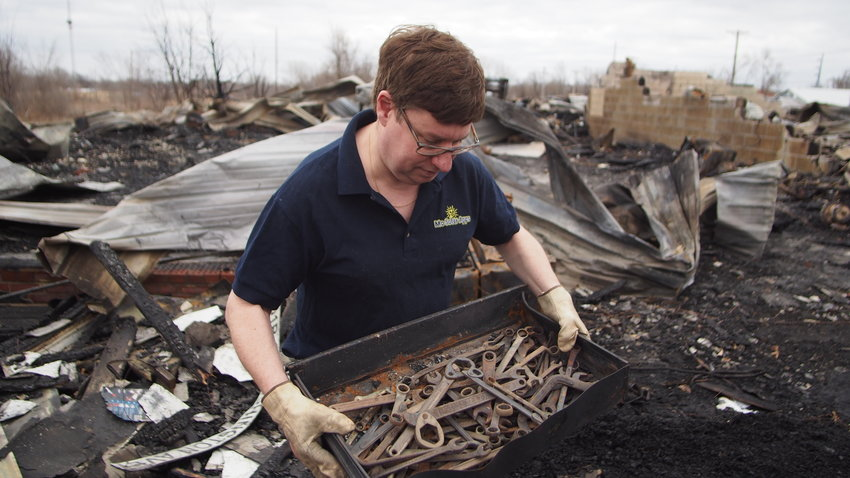 Curt Holman finds a drawer of tools Wednesday afternoon from the fire that destroyed Martinez Body Shop, 101 W. Washington Ave., on Tuesday. Not much else survived the searing heat.