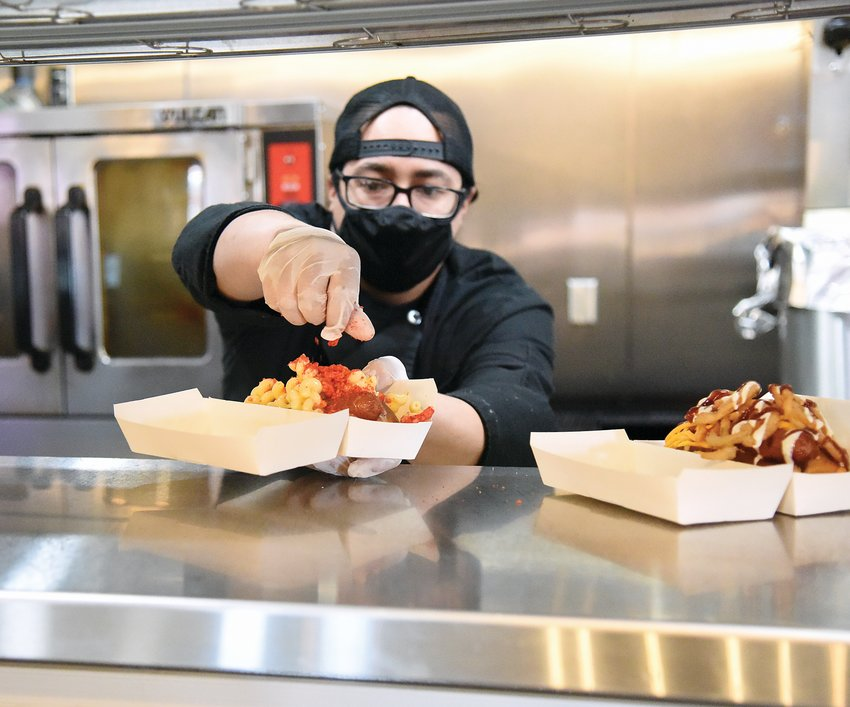 Tyler Vincent, a cook at the No. 5 Bistro and Bar at Lamy's, places the finishing touch on a Pete's Double Dawgz Mac Daddy hot dog Friday morning. Pete's Double Dawgz is a concept kitchen idea offered at Lamy's. At present, the gourmet hot dogs can only be ordered through DoorDash.