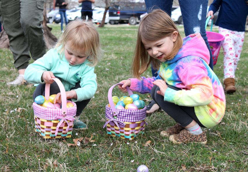 Mackenzie Burris, 4, and Peyton McKee, 3, both of Sedalia, try to find more room in their overflowing Easter baskets during Saturday morning's egg hunt hosted by Sedalia Parks and Recreation at Liberty Park.