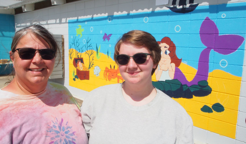 Kelly Davis, left, and daughter Dayna Davis work Monday on Dayna's mural at the Centennial Park pool.