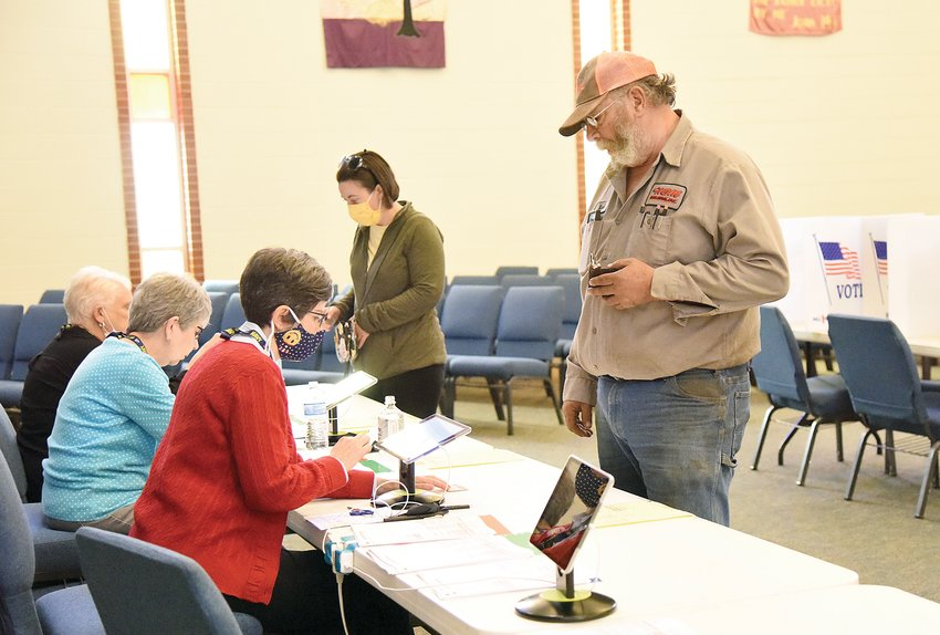 Mark Raetz prepares to vote Tuesday as Pettis County Election Judge Cynthia Decker looks over his information in Ward 3 at New Hope Baptist Church. By 11:10 a.m. 166 people had voted in the Municipal Election in Ward 3.