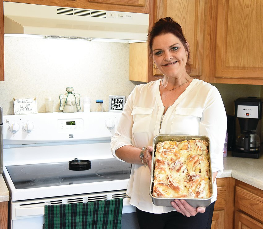 Rhea Mae Marcum, owner of Rhea Mae's Way LLC home bakery, holds a pan of her homemade orange cinnamon rolls Wednesday morning. Marcum makes a variety of home-baked goods including cookies, sweetbreads, dinner rolls and pies.