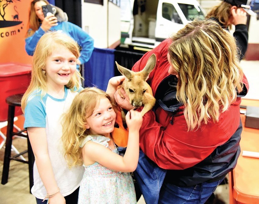 Rowyn Reed, 8, left, and Reagan Reed, 4, are all smiles as their mother, Rechelle Reed, holds a kangaroo while their father Ryan Reed takes photos Saturday at the Home and Garden Show hosted by the Democrat inside the Mathewson Exhibition Center. For $5, vendor Thorni Ridge Exotics offered visitors the opportunity to have a selfie with a kangaroo, lemur and alligator.