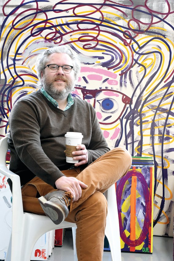 "Local artist Damon Freed sits in front of his painting ""Love,"" April 9. Freed has written several books. His most recent book of original poetry, ""The Captain's Log,"" was released April 3."