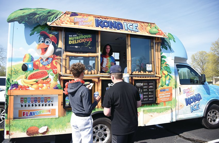 Autumn Porter with Kona Ice of Sedalia takes an order at Centennial Park Monday afternoon. After the sudden death of her husband, Noel Porter, in December, Autumn and her children made the decision to keep Kona Ice of Sedalia in business.