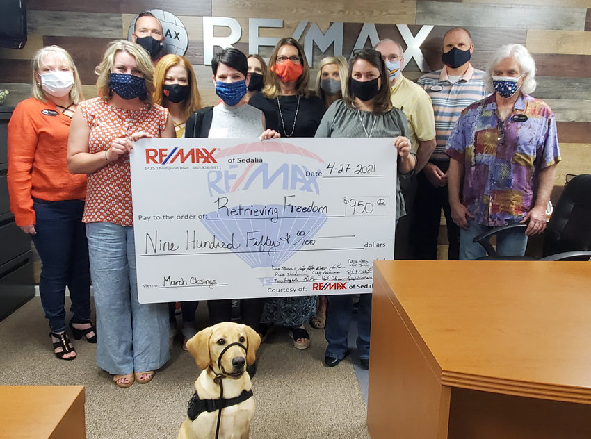 RE/MAX of Sedalia recently donated $950 to Retrieving Freedom through its Heart of Sedalia Foundation. Each month, the agents donate a portion of their earnings from every transaction to help support various local charities. Pictured are Cindy Blatterman, Dennis Hagen, Megan Grimm, Dave Wiedeman, Ryan Wiedeman, Billie Barnes, Misty Inlow, Angie Yeager, Robert Ekstrom, Dena Stockstill, Joy Wenner, Sally Zinevich. In front is Rebar, a Retrieving Freedom dog.