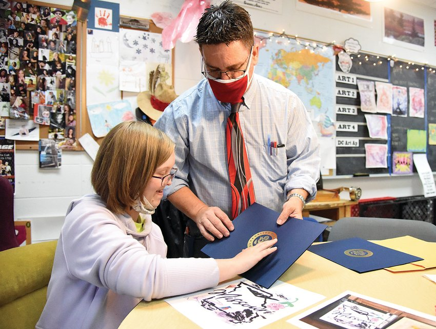 On Wednesday, Tipton High School sophomore Erica Harkins touches the seal of the U.S. Congress as her art teacher Shawn Harris holds a folder containing a certificate stating her artwork received the 2021 Congressional Art Competition People's Choice award.