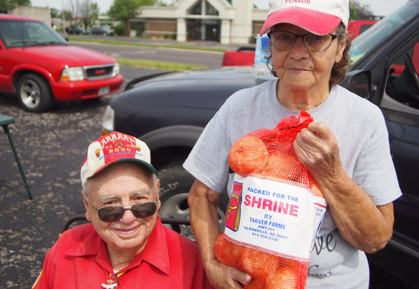 Charlie Remseyer and Shirley Willey sell Vidalia onions Monday in the Ace Hardware parking lot off of Thompson Boulevard as they have for 14 years.
