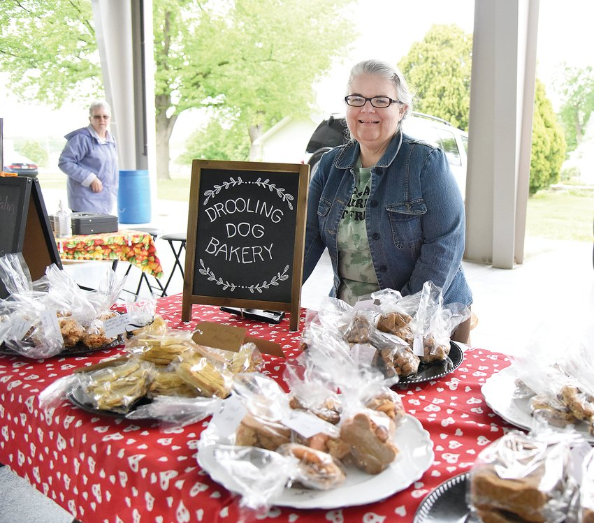 Tuesday afternoon, Christy Holmes, owner of Drooling Dog Bakery, stands with her homemade doggie treats at the Sedalia Area Farmers' Market on the Missouri State Fairgrounds. Holmes is at the market each Tuesday and Friday from 3 to 6 p.m.