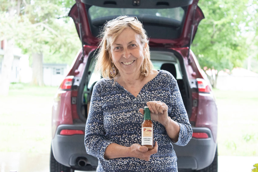 Carol Rodriguez, 71, stands with just one of the multiple reductions, sauces, and marinades she sells at the Sedalia Area Farmers' Market. Carolina's Caramel can be used to make lattes, cheesecakes, or other desserts.