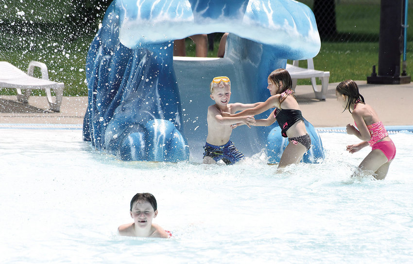 A young boy receives a helping hand after coming down a slide at Centennial Pool Tuesday, June 23, 2020. Summer sunshine and pleasant temperatures brought many people to the pool to enjoy a summer day. Centennial Park Pool, 1400 E. 16th St., is open from 1 to 6 p.m. Sunday through Thursday and from 1 to 7 p.m. Friday and Saturday.