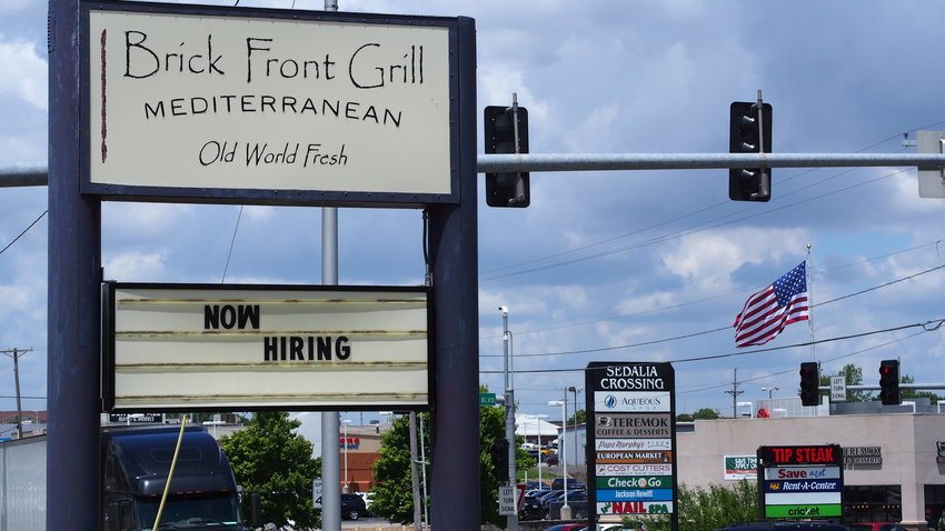 """A """"now hiring"""" sign at the Brick Front Grill, 3007 W. Broadway Blvd., is one of many seen throughout Sedalia Wednesday. Employers say they are having difficulties bringing in applicants due to the stiff local competition."""