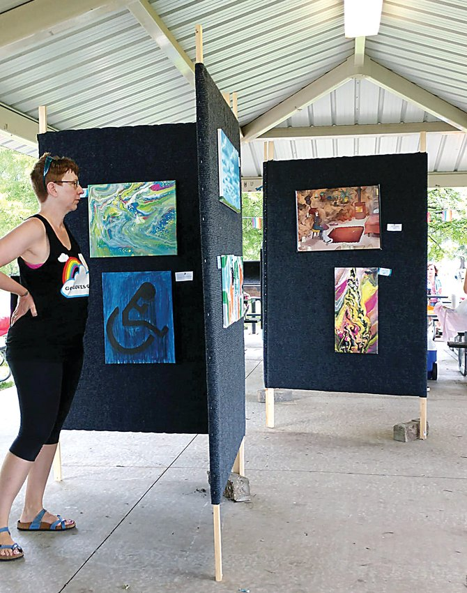 During the 2019 LBGTQ+ Pride Picnic, a woman looks over artwork displayed at the event. The second annual Pride Picnic will be hosted Saturday, July 10 at Centennial Park.