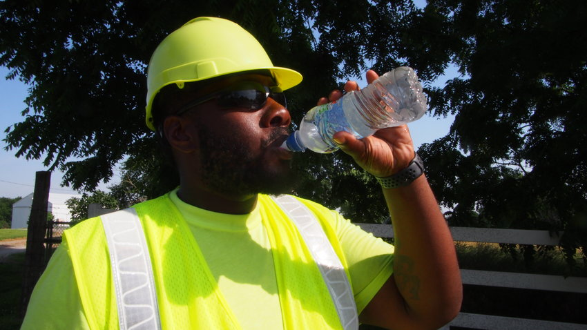 T.J. Henry drinks water while signaling traffic Friday. High temperatures may be dangerous to those suffering from dehydration.