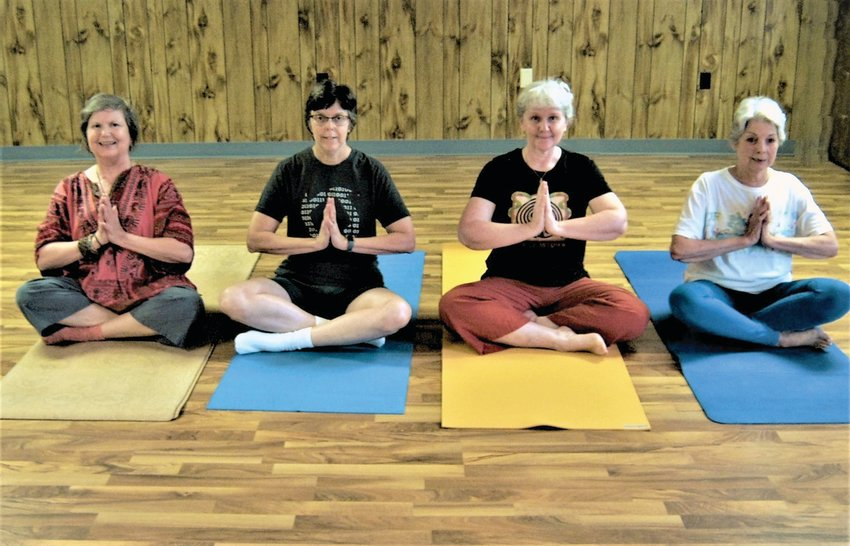 Irene Renauld, Irma Schmidt Davis, Audrey Martens Conner, Tanja Tagtmeyer, with hands in Anjali Mudra (also known as Prayer Mudra), and legs in Sukhasana (aka Easy Pose).