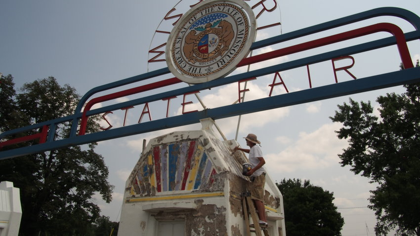 Fair employee Jack Hazell paints the entrance sign at the Missouri State Fair Wednesday.