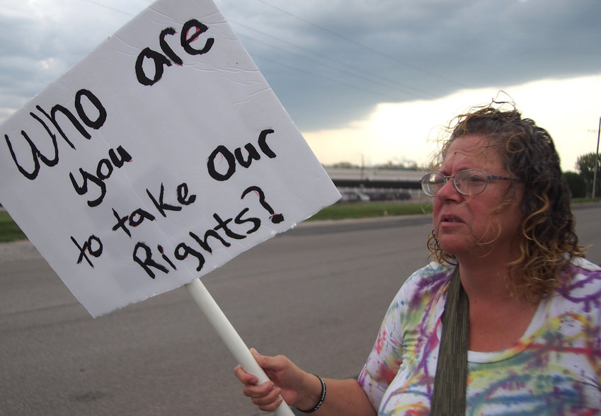 Christine Reever protests Tyson Foods's vaccine mandate Tuesday morning on Whitfield Road.