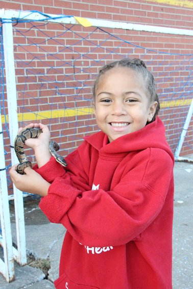 """Sariah Clemons, a preschooler at Sacred Heart School, snuggles close to her ball python, Magnolia. """"We usually bring our cats to the Blessing of the Pets, but Sariah thought Magnolia should get a blessing since she's having a hard time shedding her skin,"""" said Sariah's mom, Ileana Clemons."""