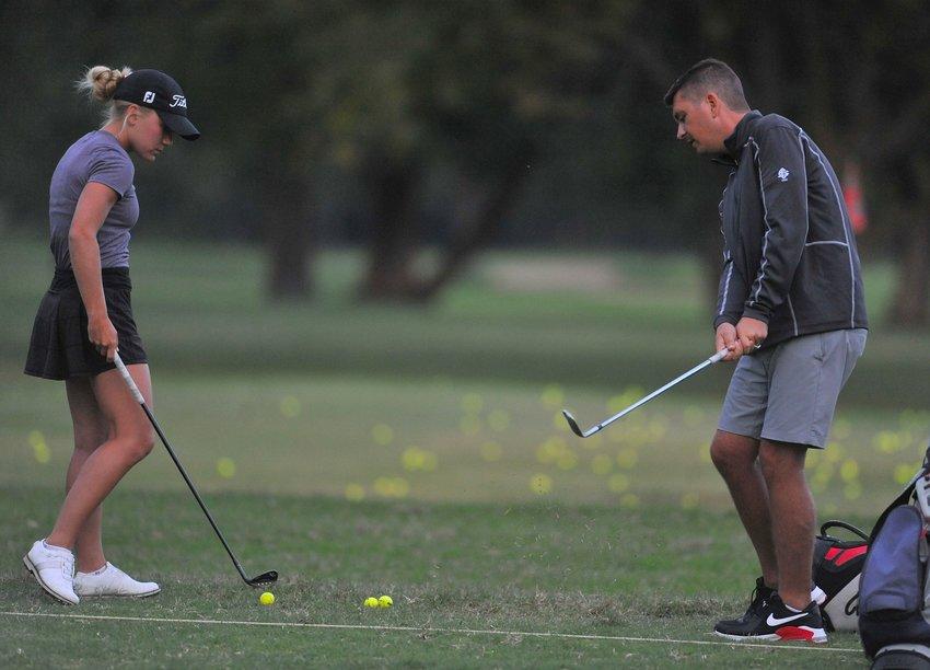 Smith-Cotton head coach Chris Guffey works with senior Kiser Pannier ahead of next week's girls golf state tournament.