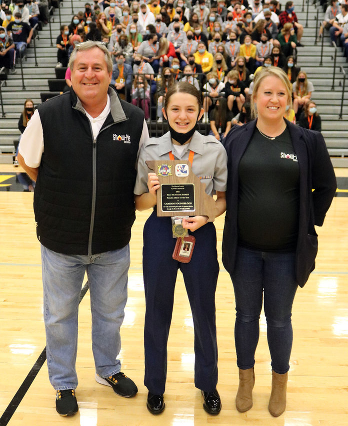 Camden Youngblood, center, a freshman at Smith-Cotton High School, is presented with the Missouri Lottery - Show-Me State Games 2021 Female Athlete of the Year award by Games Executive Director Dave Fox, left, and Program Director Jessie Sida on Friday, Oct. 15, during the S-C Homecoming assembly in the school gym.