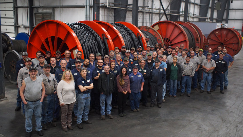 WireCo WorldGroup employees pose Thursday in front of 20,000-pound spools of 5-inch wire rope manufactured for a pit mine in Wyoming.