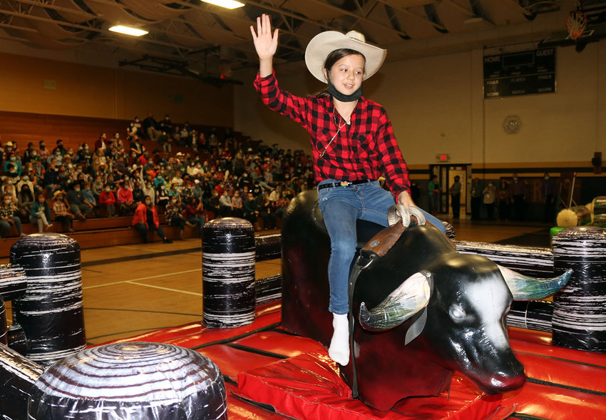 Sedalia Middle School student Ella Morey tames El Diablo to win the student mechanical bull riding competition during a rodeo-themed assembly Thursday, Oct. 21, in the SMS gym.