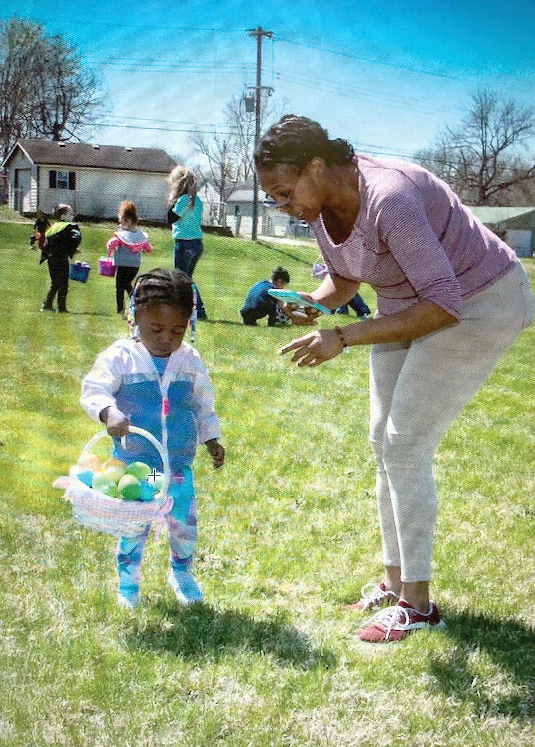 "Dynisha Hawkins, right, talks with a child about her Easter eggs during the NORTH organization's third annual Easter Egg Hunt Saturday at Hubbard Park. Close to 200 children ages 1 to 17 attended the event that also offered hot dogs, chips and drinks. Names were also drawn for 40-plus Easter baskets that were donated by ""So Sick Crew."""
