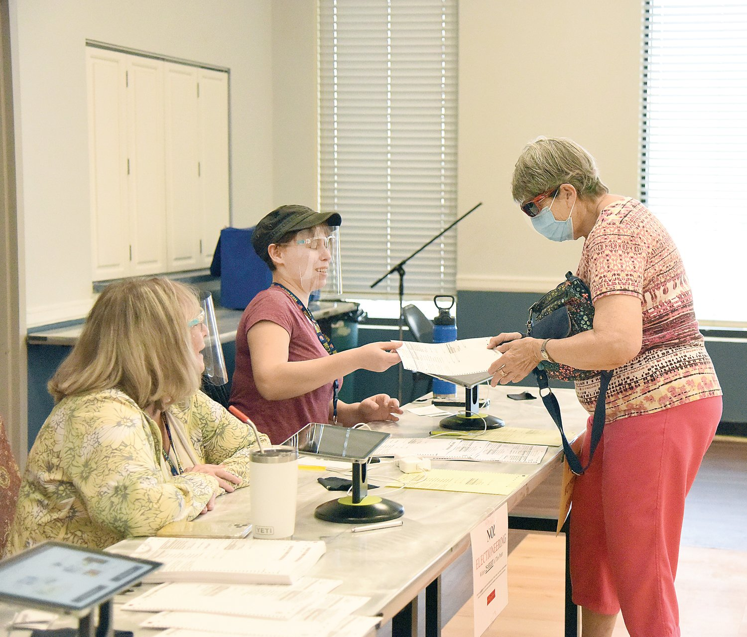 Mary Louise Dove receives her ballot from Pettis County Election Judge Allison McIntyre on Tuesday for Ward 4 at the United Methodist Church Celebration Center. At 10:51 a.m. 222 people had voted in Ward 4.
