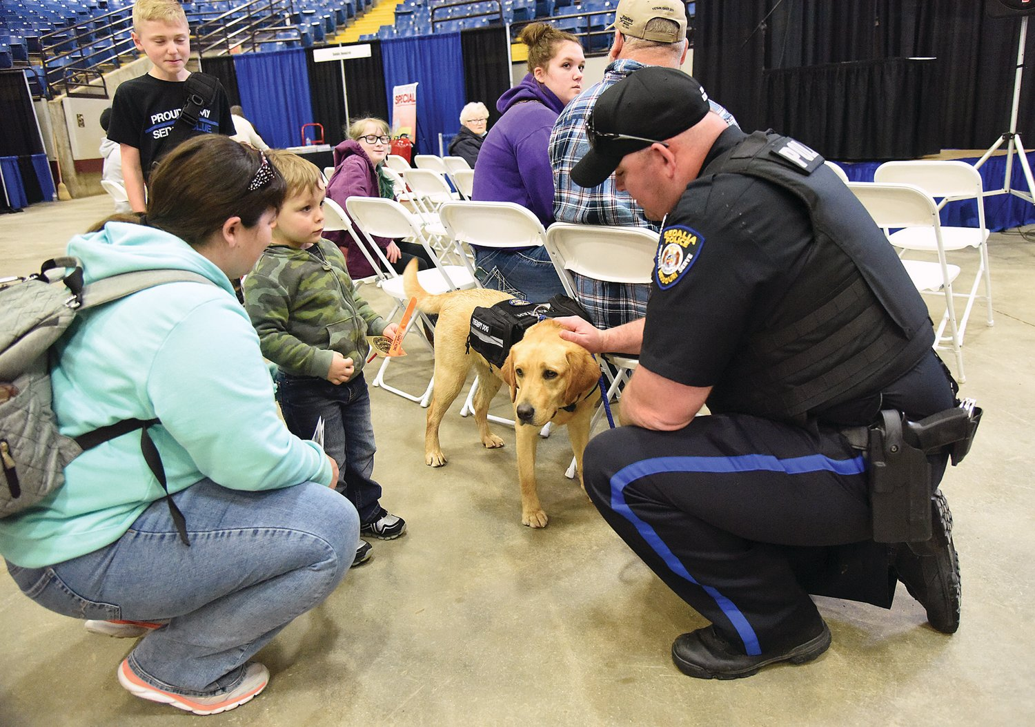 "Sedalia Police Officer Antonio Karr and SPD therapy dog Kyah visits with Jackson Harbison, 3, and his mother, Victoria Harbison, of Sedalia, at the Home and Garden Show on the Missouri State Fairgrounds. SPD Sgt. Casey DeVorss said Kyah is new to the department and belongs to everyone. He added Kyah will bridge the gap between SPD and the community and ""humanize the badge."""