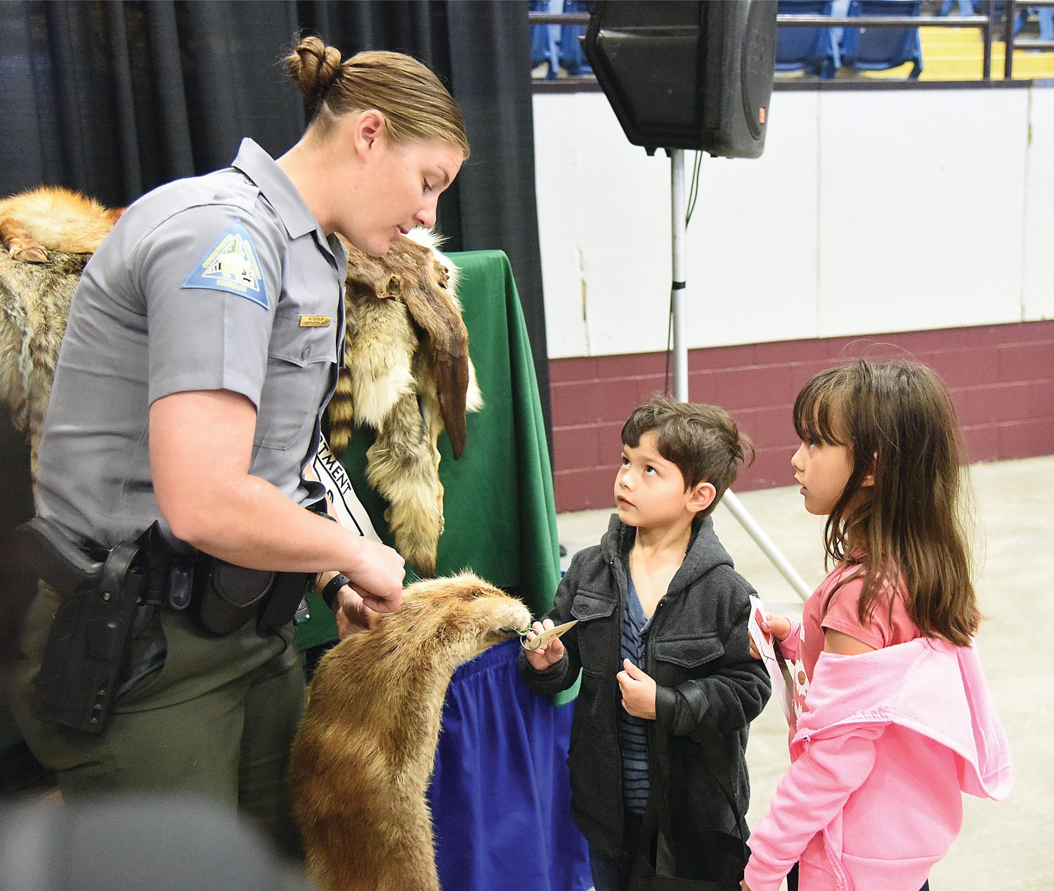 Missouri Department of Conservation Pettis County Agent Haeley Eichler holds an animal pelt for Matthew Goodman, 6, and Evelyn Goodman to touch Saturday at the Home and Garden Show. The children were attending the event with their mother, Reni Dietrick, and their step-father, Brian Patton.