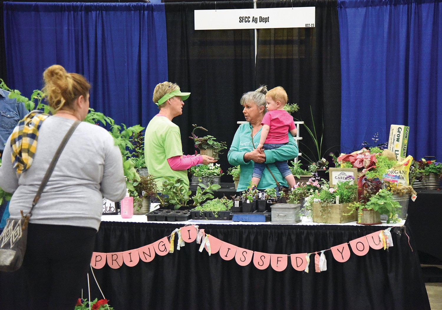 State Fair Community College Ag Instructor Kim Rimel talks with a woman Saturday at the Home and Garden Show. SFCC offered a variety of plants and flowers for sale at the event.