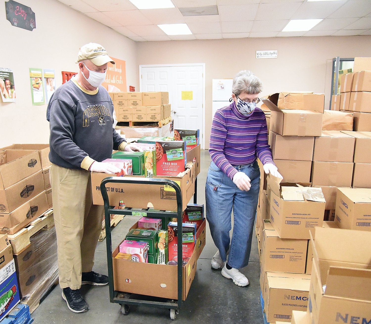 Open Door Pantry volunteers Richard and Karen Parker, of Sedalia, work to load boxes with canned goods this week at the panty.