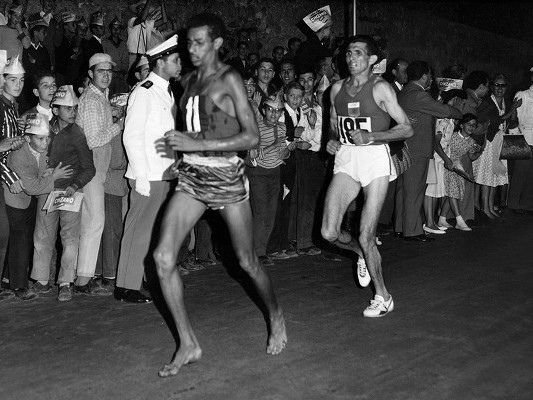 Abebe Bikila running barefoot at the 1960 Olympics in Rome.  The Ethiopian native took gold in that race, crossing the finish line in a record time of 2:15:16.