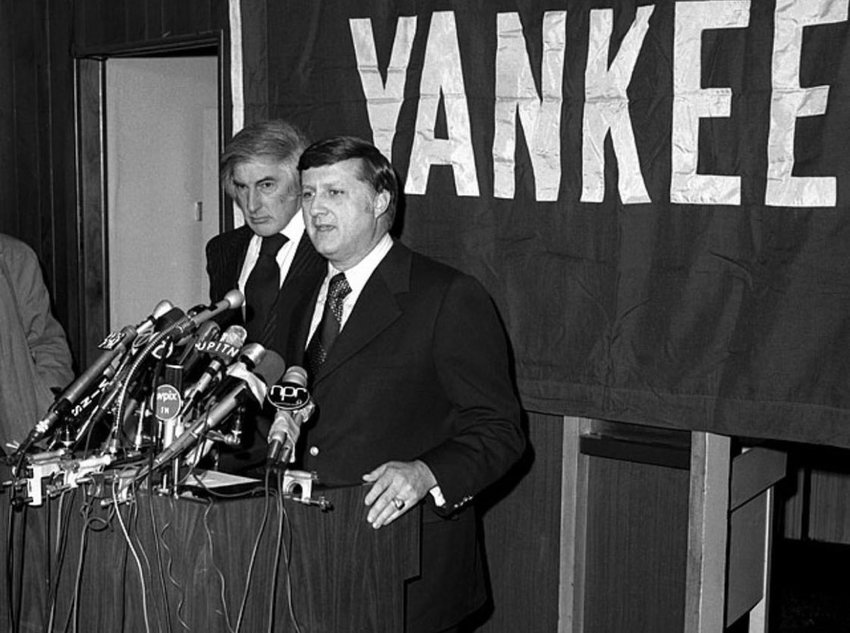George Steinbrenner and Michael Burke (standing behind) announcing their purchase of the New York Yankees for $10 million on January 4th, 1973. The following year, Burke would be out the door as senior executive of the team and Steinbrenner would begin his imperious ownership of the club, turning the Yankees brand into today's $5 billion sports property.