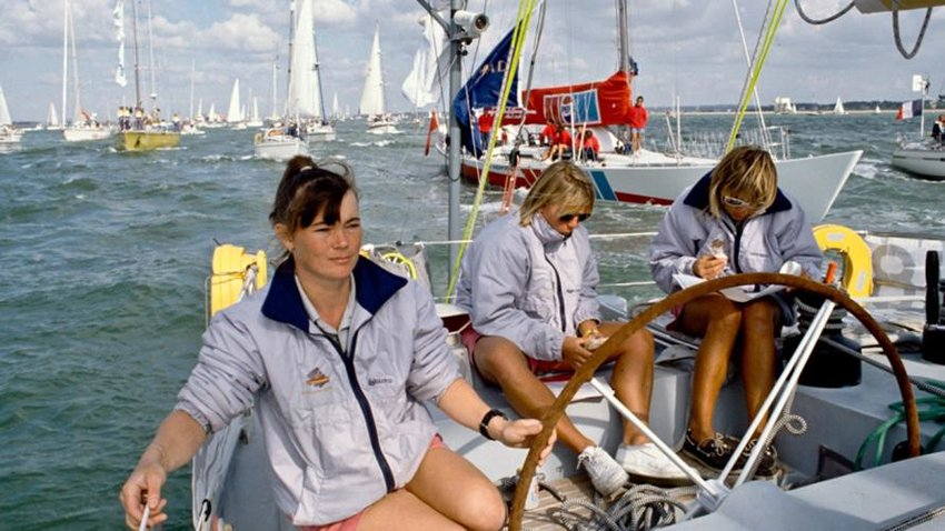 Tracy Edwards at the helm of the 'Maiden' with two of her crew members behind. In 1989, she made history by becoming the first woman to skipper an all-female team at the Whitbread Round the World Race, earning her the Yachtsman of the Year Trophy.