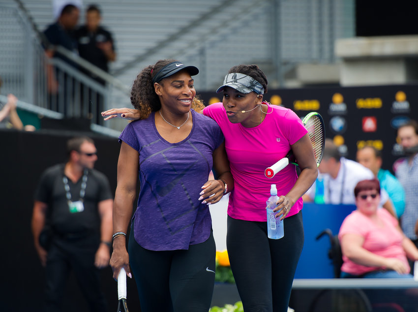 "Venus (right) and Serena Williams, the most successful sibling act in sports history. Cecil Harris is author of a new book, ""Different Strokes: Serena, Venus, and the Unfinished Black Tennis Revolution"". The book is available for sale on our website."
