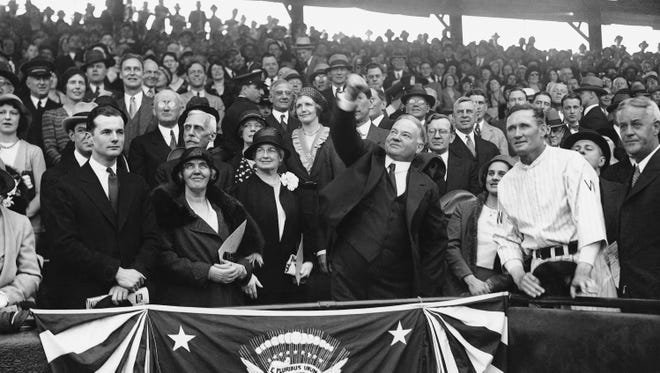 President Herbert Hoover throwing the ceremonial first pitch on April 14, 1931 in a game between the Washington Senators and Philadelphia Athletics. To his left is former pitcher and now Senators manager, Walter Johnson. A lover of baseball, Hoover attended more MLB games than any other American President.