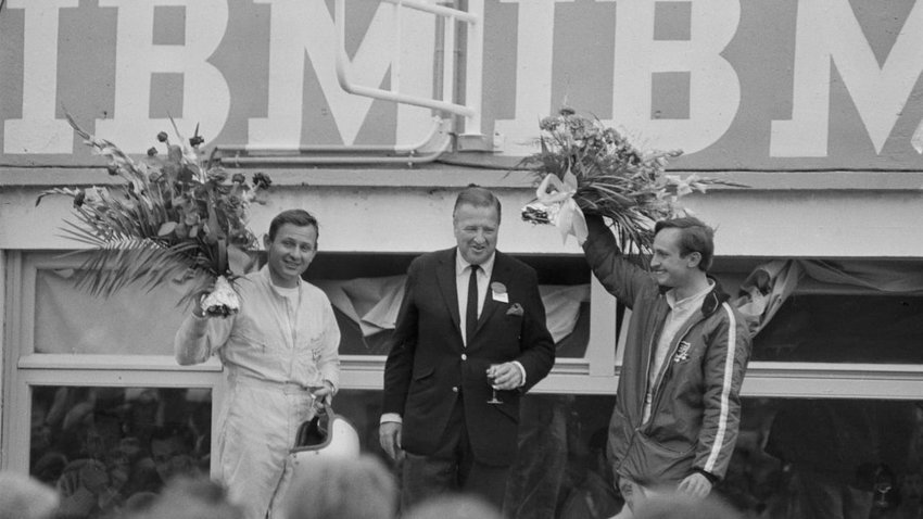 Henry Ford II standing center with Bruce McLaren (left) and Chris Amon (right), winners of the 1966 24 Hours of Le Mans. The victory ended Ferrari's long-running dominance of the endurance race and Ford's personal quest to dispatch the Italian company on their own European turf.