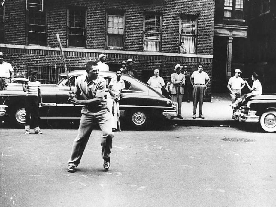 Willie Mays playing stickball on the streets of Harlem in the 1950s. A familiar urban scene for most of the 20th century, stickball by the 1980s gave way to shifting cultural patterns and more recreational options.