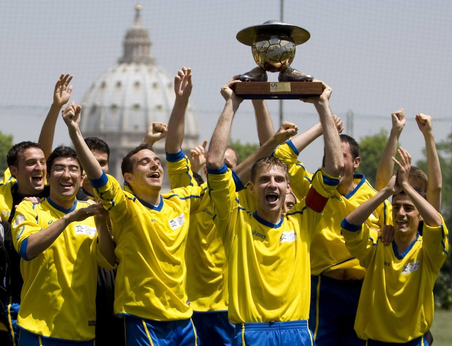 "Hoisting the ""Clericus Cup"" trophy with St Peter's Dome in the background."