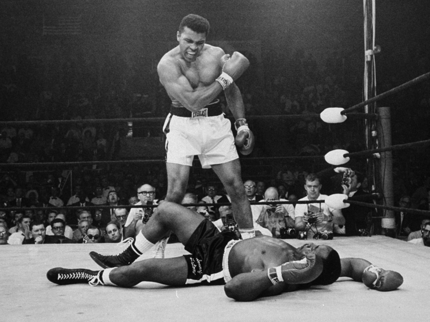 "Muhammad Ali towering over a floored Sonny Liston.  Speculation remains rife that Liston took a dive on a ""phantom punch""."