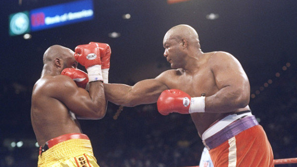 George Foreman lands a punch on Michael Moorer at their 1994 world heavyweight title bout.  45-year old Foreman, an ordained minister since 1978, won his 2nd title after a record 20-year hiatus.