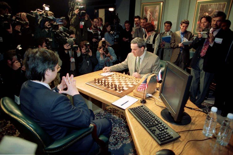 World chess champion Gary Kasparov at the 1997 rematch against IBM's Deep Blue supercomputer.  Moving the pieces for the machine is Feng siung-Hsu, one of Deep Blue's original developers.  The historic 6-game rematch which ended in a score of 3.5-2.5 was the first time a computer defeated a world champion under official tournament regulations.