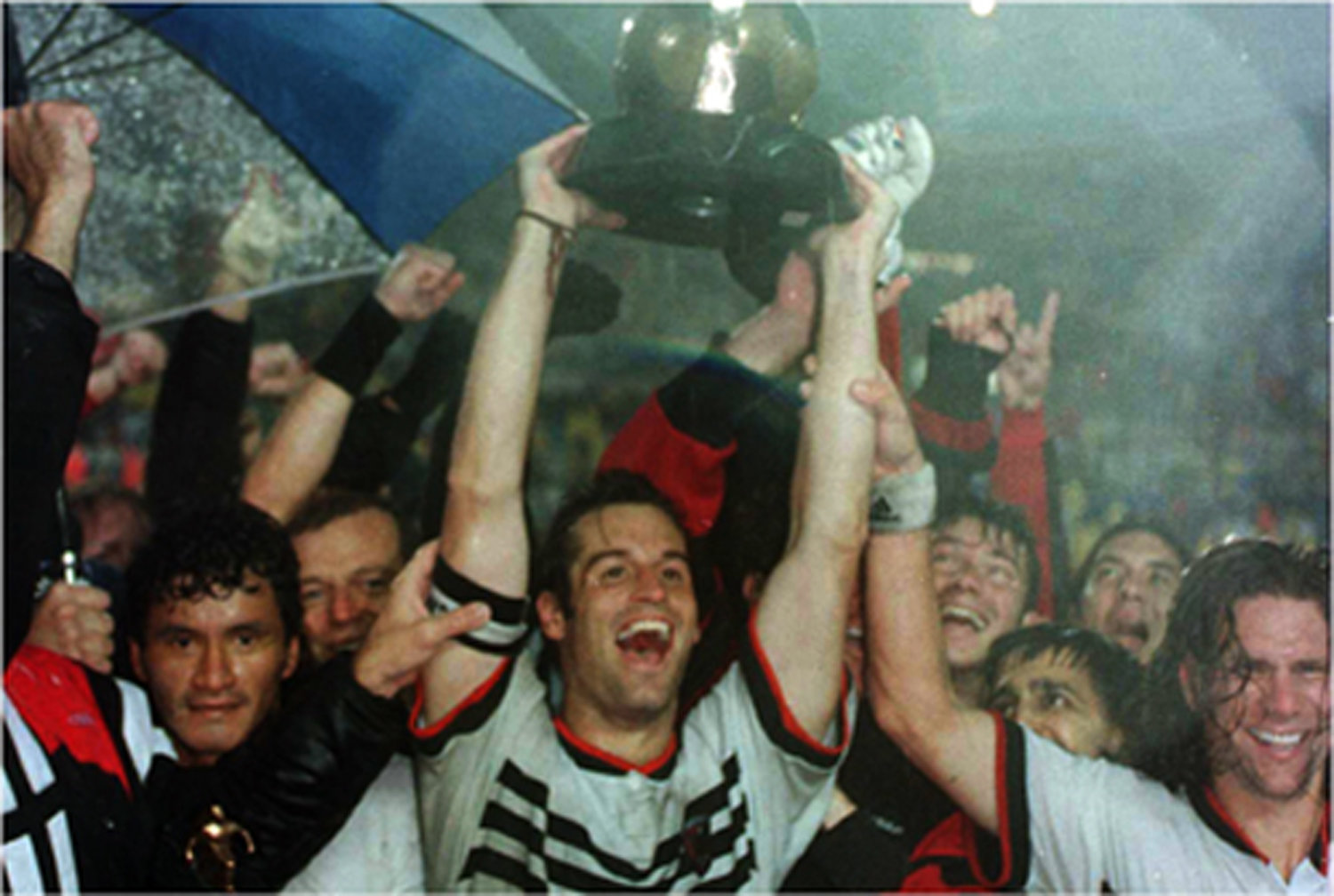 John Harkes of D.C. United hoisting the trophy after his team defeated the LA Galaxy 3-2 in the first ever championship match of Major League Soccer (1996).  Despite the initial euphoria, soccer enthusiasm in America quickly waned and MLS would come close to folding before surging in a remarkable comeback.