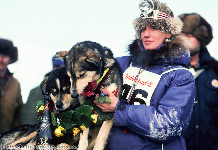 Libby Riddles with dogs Axle and Dugan after taking first place at the 1985 Iditarod dog sled race. Braving 1,000 miles across the Alaskan wilderness, Libby was the first woman to win the prestigious arctic chase, crossing the finish line in 18 days and 20 minutes.