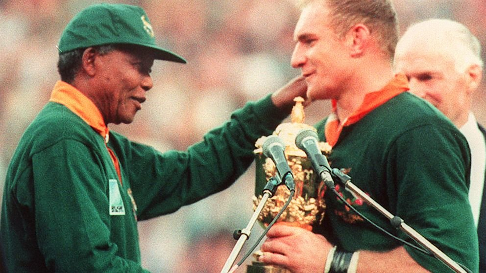 Nelson Mandela congratulating team captain, Francois Pienaar, for winning the 1995 Rugby World Cup. Wearing the Springboks' shirt and cap, a symbol of apartheid for many South African blacks, Mandela helped reconcile a broken nation with the unity of sport.