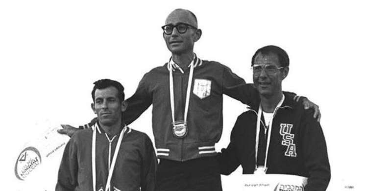 Shaul Ladani (center) receiving his gold medal at the 1969 Maccabiah Games. A survivor of the Holocaust and the Munich Massacre, Ladany was a 2-time Olympian and former world champion in the 100-km racewalking event. He still holds the world record for the 50-mile race, which has remained unbroken since 1972.